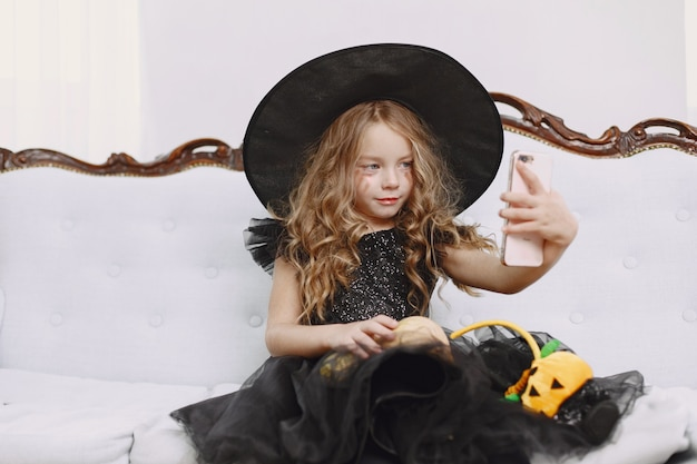 Smiling happy positive little girl witch in carnival halloween costume