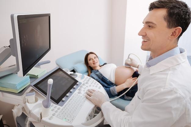 Улыбающийся счастливый позитивный медик, работающий в клинике, проводящий ультразвуковое сканирование брюшной полости беременных с использованием профессионального оборудования