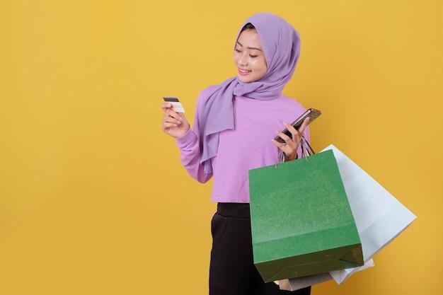 신용 카드를 사용하여 쇼핑몰에서 돈을 낭비하고, 쇼핑백을 들고, 선물이나 선물을 구입하고, 하루를 치료하고, 휴대 전화를 들고, 신용 카드를 사용하여 웃는 행복한 예쁜 소녀
