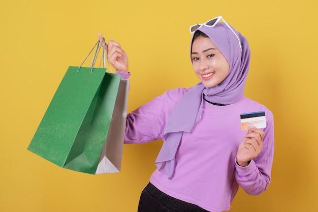 신용 카드를 사용하여 쇼핑몰에서 돈을 낭비하고, 쇼핑백을 들고, 선물이나 선물을 구입하고, 하루를 치료하고, 즐겁게 웃고 웃는 행복한 예쁜 소녀