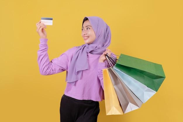 신용 카드를 사용하여 쇼핑몰에서 돈을 낭비하고, 쇼핑백을 들고, 선물이나 선물을 구입하고, 하루를 치료하는 웃는 행복 예쁜 소녀