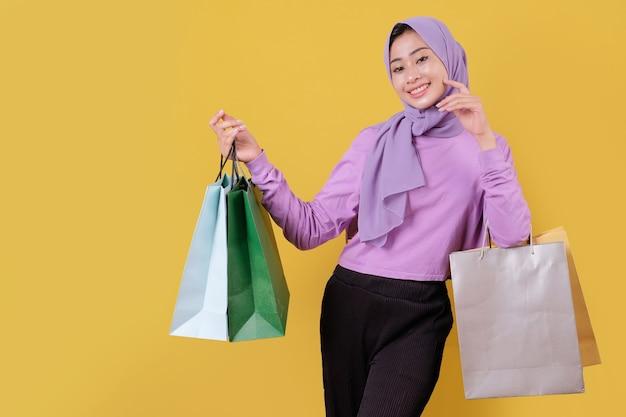 Улыбающаяся счастливая красивая девушка, использующая кредитную карту, чтобы тратить деньги в торговом центре, держа сумки для покупок, покупать подарки или подарки, баловать себя днем