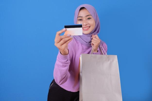 クレジットカードを使ってショッピングモールでお金を無駄にしたり、買い物袋を持ったり、ギフトやプレゼントを買ったり、一日を過ごしたりする幸せなかわいい女の子の笑顔