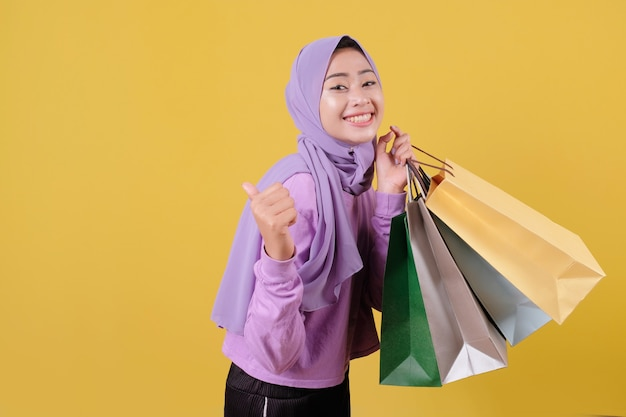 Smiling happy pretty girl using credit card to waste some money in mall, holding shopping bags, buy gifts or presents, treat yourself day, laughing joyfully