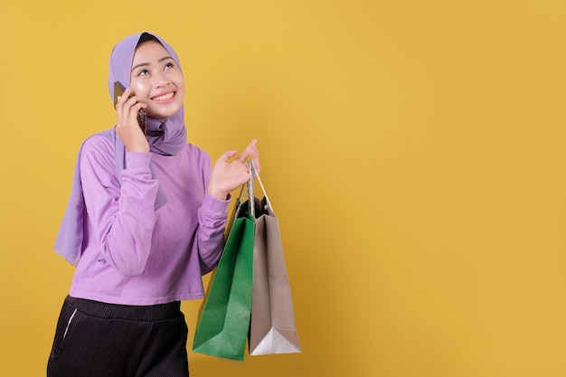 Smiling happy pretty girl using mobile phone, online shopping, bring a bag, cheerful and joyful
