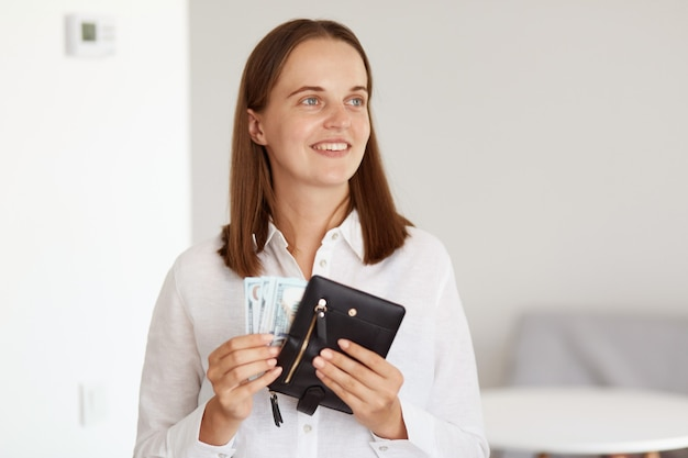Smiling happy rich dark haired female wearing white casual style shirt, standing with black wallet with money in hands and lookig away with dreamy expression.