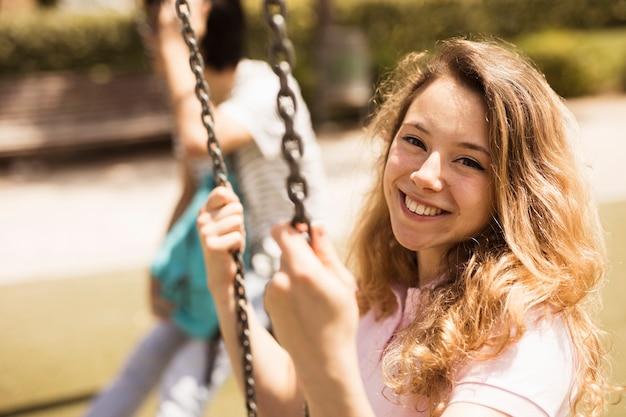 Улыбающаяся счастливая школьница сидит на качелях