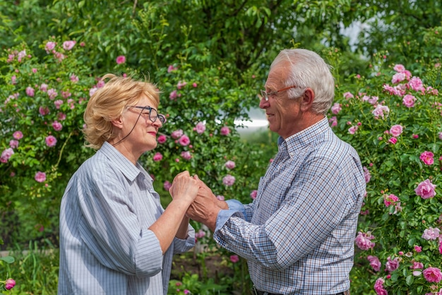 幸せな年配の女性と手をつないで笑顔。春または夏の晴れた日。