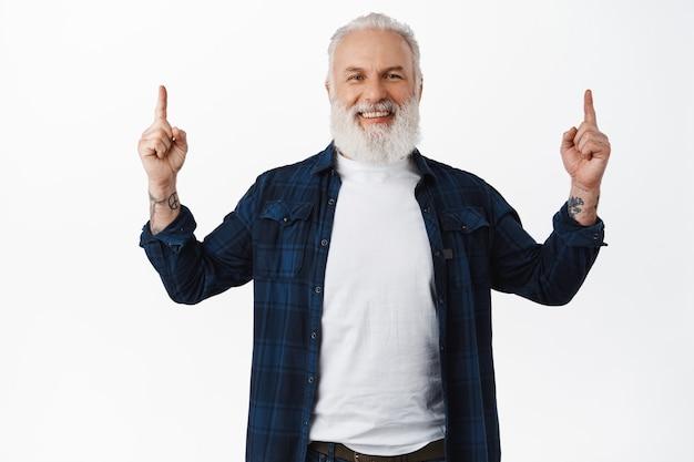 笑顔の幸せな年配の男性が指を上に向けて笑い、広告を表示して推奨し、ウェブページをデモンストレーションし、白い壁にスタイリッシュな服を着て立っています