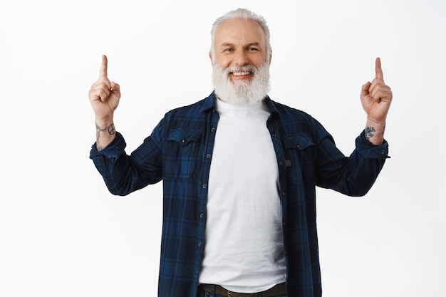 Smiling happy senior man pointing fingers up and laughing, showing and recommending advertisement, demonstrate webpage, standing in stylish clothes against white wall