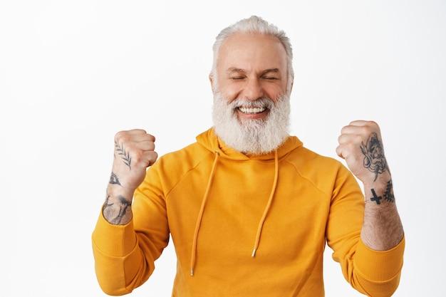 Sorridente uomo anziano felice che trionfa, celebra vittoria e vittoria, fa pompa a pugno con gioia, sembra allegro dopo aver vinto denaro, ha ottenuto un premio, in piedi sul muro bianco