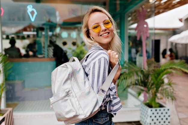 Sorridente ragazza alla moda felice in spettacoli alla moda rotondi che indossa camicia spogliata