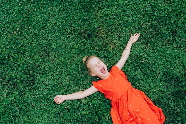 Smiling happy toddler girl wearing red dress lying on green grass with her arms outstretched. space for message.