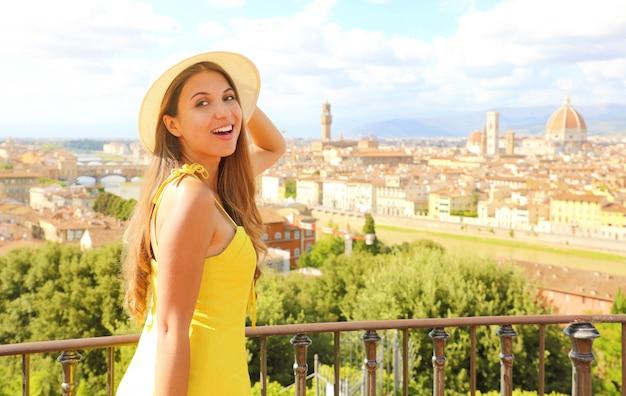 Улыбается счастливая туристическая девушка во флоренции, италия. портрет молодой женщины, посещающей красоту тосканы в италии.