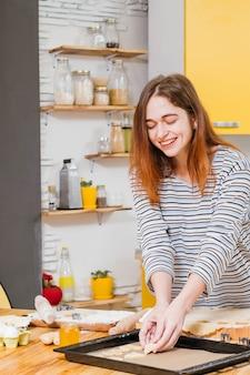笑顔の幸せな女性がキッチンでクッキーを焼く