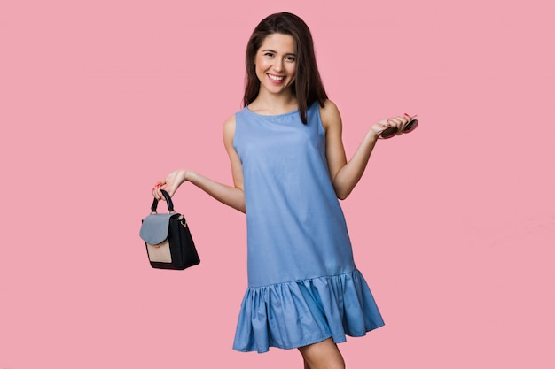 Smiling happy woman in blue summer cotton dress posing on pink background, holding purse and sunglasses, vacation style, young and beautiful