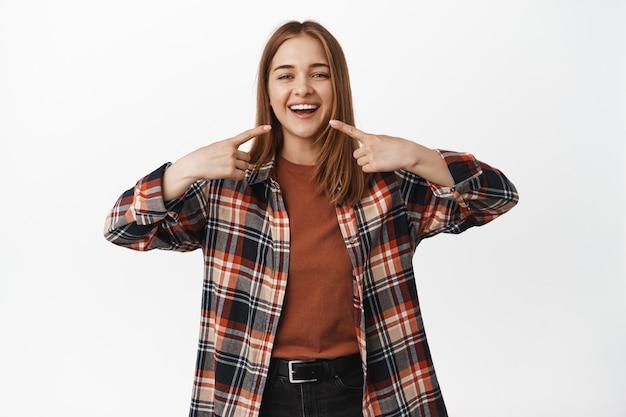 笑顔の幸せな女性が歯科医院でホワイトニングをし、満足のいく笑顔で口を指さし、口内科医を推薦し、白い壁に立って
