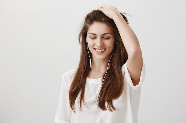 Donna felice sorridente che gode dell'ascolto della musica in auricolari