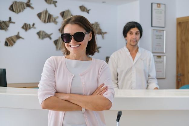 Улыбающаяся счастливая женщина-гостья в фойе курортного спа-отеля
