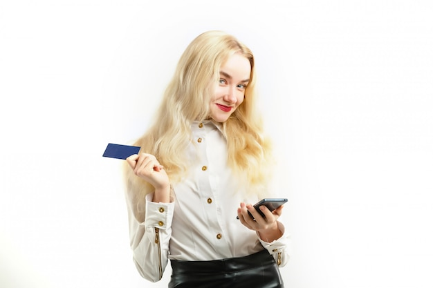 Smiling happy woman holding credit card and mobile phone while looking at camera
