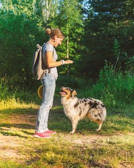 Улыбающаяся счастливая женщина в повседневной одежде играет с собакой в парке в летний день
