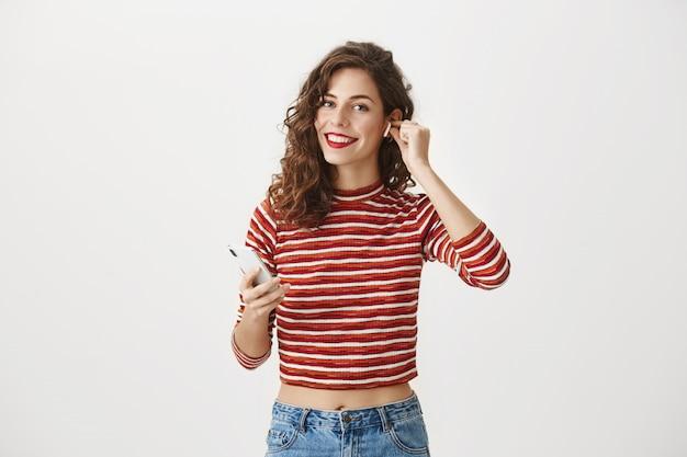 Donna felice sorridente che ascolta la musica in auricolari wireless, utilizza l'app per smartphone