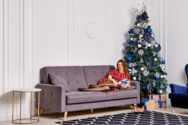 크리스마스 트리 근처 소파에 누워 웃는 행복 한 여자