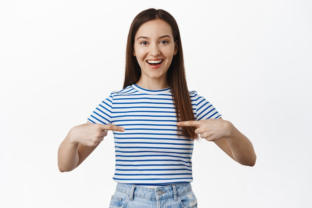 Smiling happy woman pointing fingers at center, empty space against her chest and looking excited, show sale, standing over white wall