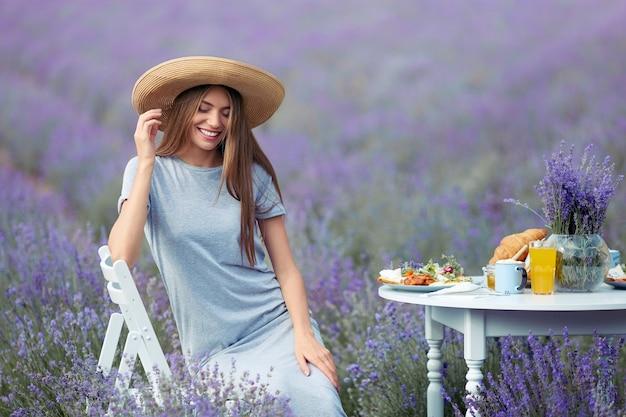 ラベンダー畑でポーズをとって幸せな女の笑顔