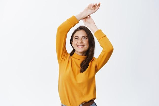 Улыбающаяся счастливая женщина поднимает руки вверх с беззаботными и расслабленными эмоциями, стоя у белой стены в повседневной одежде