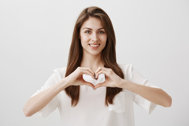 Smiling happy woman showing heart gesture