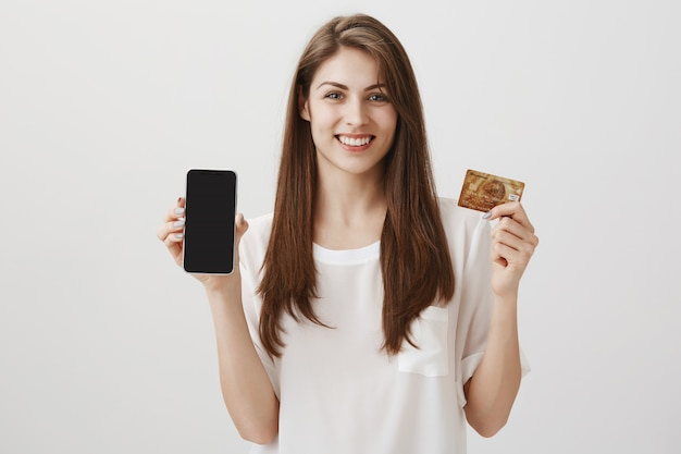 Smiling happy woman showing mobile phone display and credit card. promo of shopping application