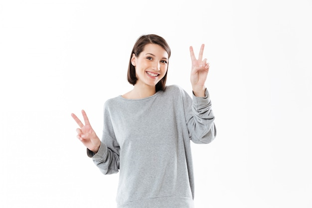 Улыбается счастливая женщина, показывая мирный жест двумя руками