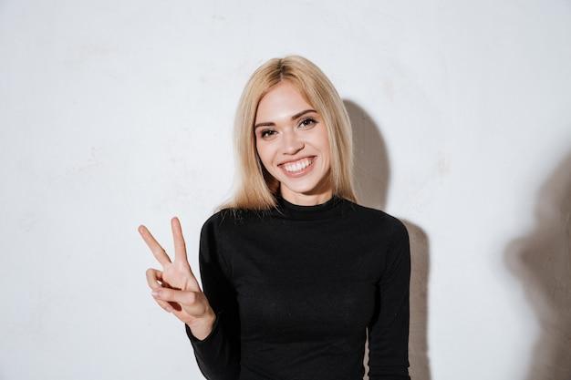 평화 기호를 표시하고 카메라를보고 웃는 행복 한 여자