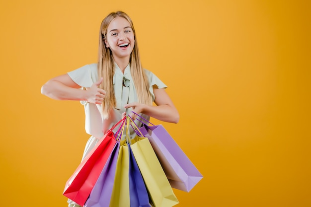 Smiling happy woman showing thumbs up with colorful shopping bags isolated over yellow