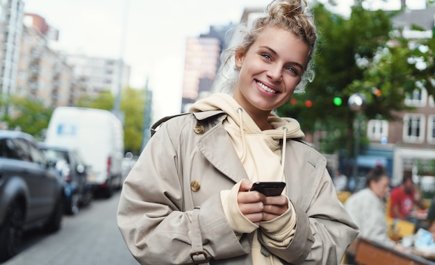 Улыбается счастливая женщина, стоя на улице с мобильным телефоном.