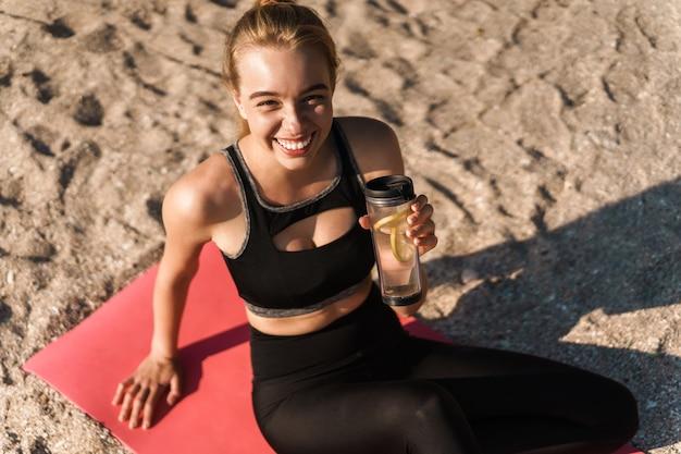 아침에 해변에서 매트에 요가 운동 후 tracksuit 식수를 입고 웃는 행복 한 여자