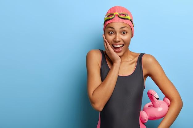 Улыбающаяся счастливая женщина носит купальный костюм и резиновую шапочку