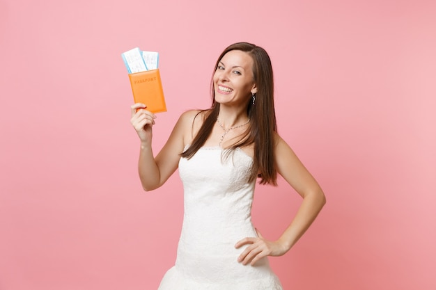 Smiling happy woman in white dress holding passport and boarding pass ticket, going abroad, vacation