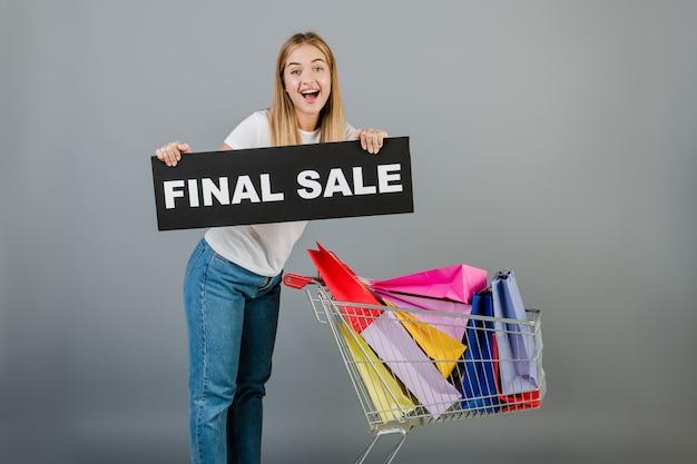 Улыбается счастливая женщина с окончательной продажи знак и тележка с красочными сумок, изолированных на серый
