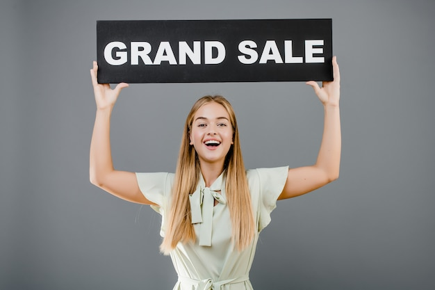 Smiling happy woman with grand sale sign isolated over grey