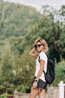 Smiling happy woman with short hairstyle dressed white t-shirt and shorts in black sunglasses traveling in mountains, good sunny day, hiking in the mountains