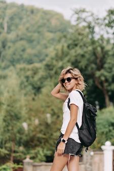 Donna felice sorridente con t-shirt bianca vestita di acconciatura corta e pantaloncini in occhiali da sole neri che viaggiano in montagna, buona giornata di sole, escursioni in montagna