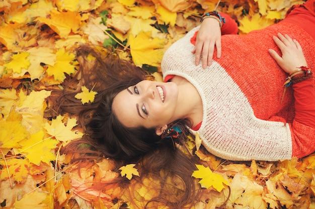 秋の葉で横になっている笑顔の幸せな女性の肖像画