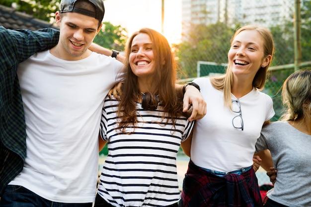 笑顔の幸せな若い大人の友人の腕の周りの肩の屋外の友情と接続の概念