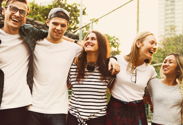 Smiling happy young adult friends arms around shoulder outdoors friendship
