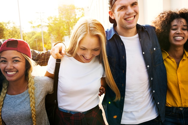 Smiling happy young adult friends arms around shoulder walking outdoors