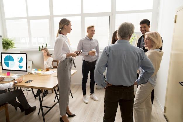 Улыбающиеся счастливые молодые и старшие офисные работники говорят в коворкинг