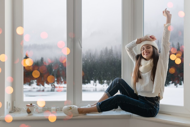 Улыбающаяся счастливая молодая привлекательная женщина в стильном белом вязаном свитере, шарфе и шляпе, сидя дома на подоконнике на рождество, веселится, взявшись за руки, вид на зимний лес, огни боке