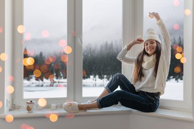세련 된 흰색 니트 스웨터, 스카프와 모자 크리스마스에 창턱에 집에 앉아 웃 고 행복 한 젊은 매력적인 여자 손을 잡고 재미, 겨울 숲 배경보기, 조명 bokeh